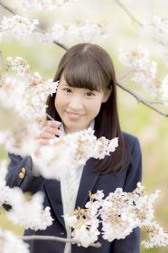 桜の下でほほ笑む女子高生