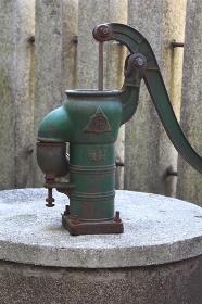 都会の下町の神社の境内にある井戸とポンプ