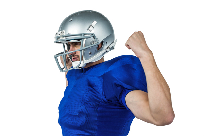 Confident American football player flexing muscles