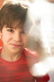 Portrait of a charming joyful boy in a red T-shirt with sunbeams