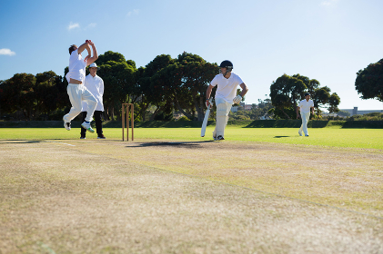 Players playing cricket match at field