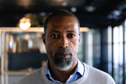 Portrait of an African American businessman wearing smart clothes, working in a modern office, looking straight into a camera.