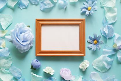 青を基調とした造花と背景。中央に横長の木製フォトフレームの中に白いコピースペース。平置きの俯瞰撮影。