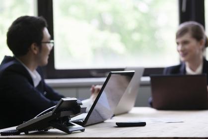パソコンをしながら談笑するビジネスパーソン
