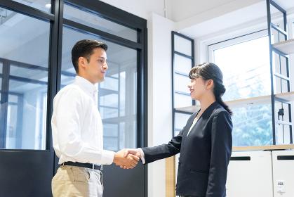 握手をする男性と女性(人種の違う人々)