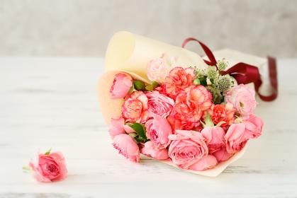 グレーの背景にピンクのバラとカーネーションの花束