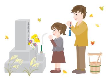 秋のお彼岸にお墓参りをする父と娘