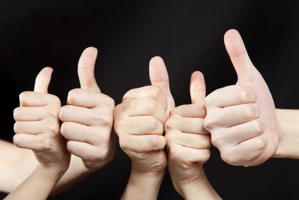 親指を立てる男女の手