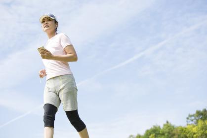 走りながら音楽を聴く中年女性