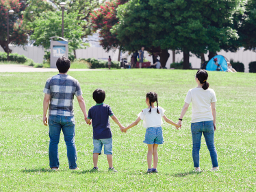 緑の芝生の公園で手をつなぐ家族
