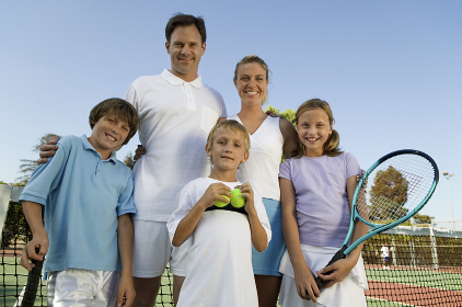 Family on Tennis Court by net portrait front view