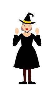ハロウィンの仮装、魔女姿の女の子が両手を構えて驚かせるポーズ