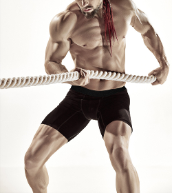 Muscular man working out with heavy ropes. Photo of sporty male with naked torso