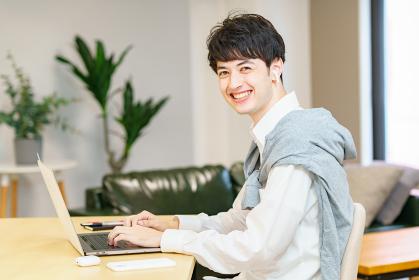 カジュアルな空間でノートパソコンを使う若い男性