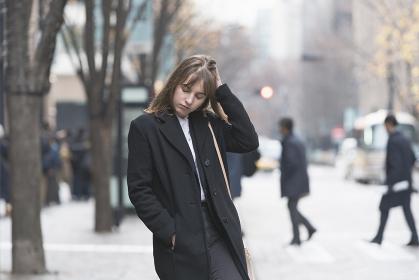街で待ち合わせをする女性