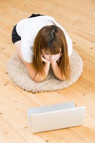 部屋でパソコンを見る女性 考える