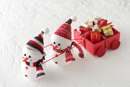 クリスマスに箱いっぱいに積んだプレゼントを運んでくるゆきだるま達と雪景色