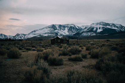 old cabin sits in a desert valley with snow covered mountains behind