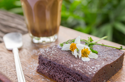 Chocolate Brownie Cake and Coffee and Daisy on Chopping Board on Wood Table Right
