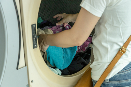 コインランドリーで洗濯物を取り出す女性