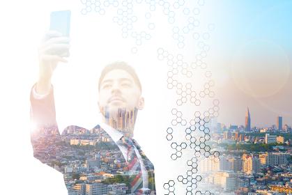 スマートフォンを持つビジネスマンと都市風景の合成写真