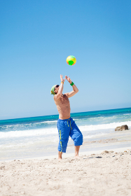 young sporty man in jump at beach volleyball