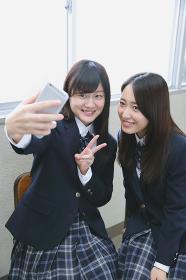 スマートフォンで自撮りする女子高生