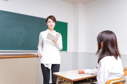 本を持って授業をする女性教師
