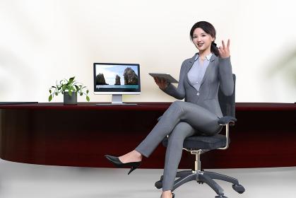 カウンター風のテーブルにパソコンを置き足を組んだスーツの女性社員がタブレットを片手にピースサインする
