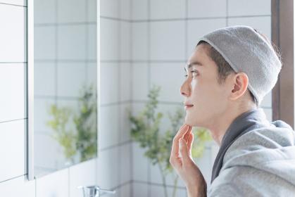 洗面台でフェイスケアをする若い男性・化粧水と洗顔