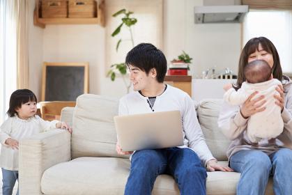 ソファでパソコンを見るアジア人ファミリー