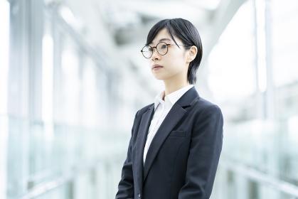スーツを着て、緊張した表情をしている若い女性