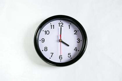 白い壁に掛かった4時の時計