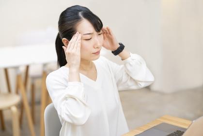 仕事中、頭痛に悩む女性