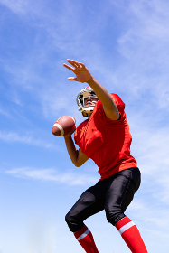 Low angle front view of a mixed race male American football player wearing a team uniform, training at a sports field, preparing to throw a football, with blue sky in the background