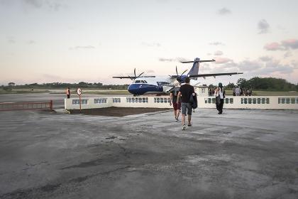 早朝、小型旅客機に乗り込む旅行客