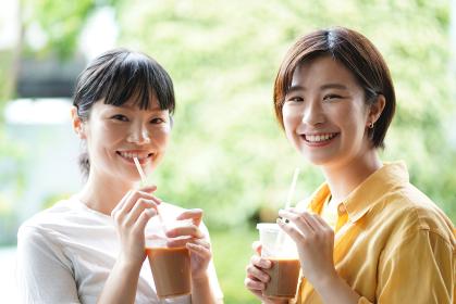 飲み物を飲みながら会話する女性