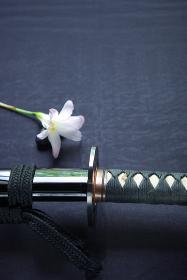 鞘に納まった居合練習刀と清楚な花一輪