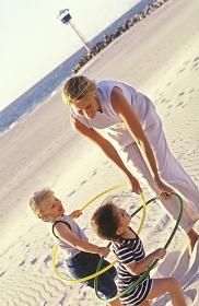 Portrait, Strandszene, Mutter spielt mit ihren 2 3-4-jaehrigen Toechtern mit bunten Hoola-Hoop Reifen