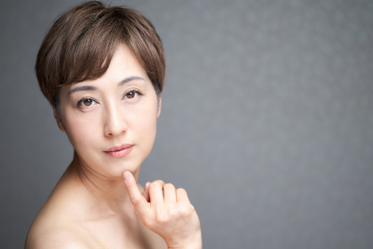 カメラ目線で顎に指をあてる中年の日本人女性