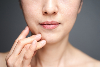 頬杖をついて悩む中年の日本人女性