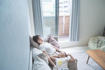 自宅のソファで昼寝する親子