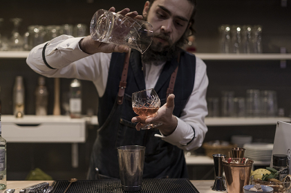 Barman in shirt and apron making an alcoholic drink with ice in a cocktail glass