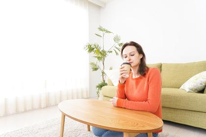 家でコーヒーを飲む若い女性