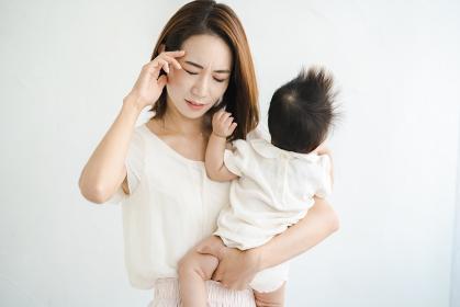 赤ちゃんを抱えて、疲れた表情をするお母さん