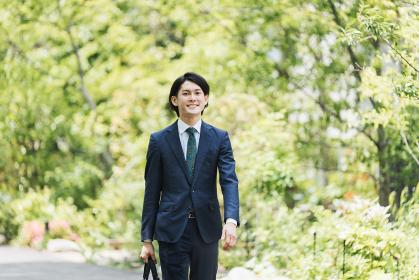 通勤中のビジネスマン・新緑の中の男性のビジネスシーン