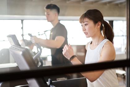 トレーニングジムでランニングマシンで走るアジア人女性