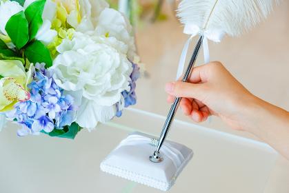 チャペルの祭壇の羽ペンを持つ手 結婚証明書 サイン