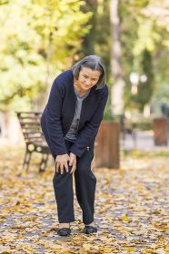 Senior woman having knee pain walking in park