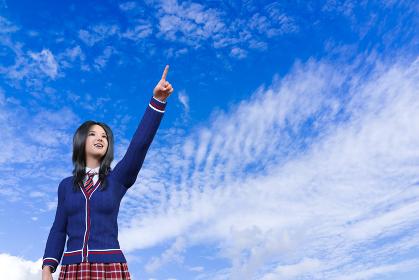 うろこ雲が浮かぶ秋の青空に指をさし目標に向かって希望に満ち溢れた笑顔を浮かべる青いセーターの女子高生